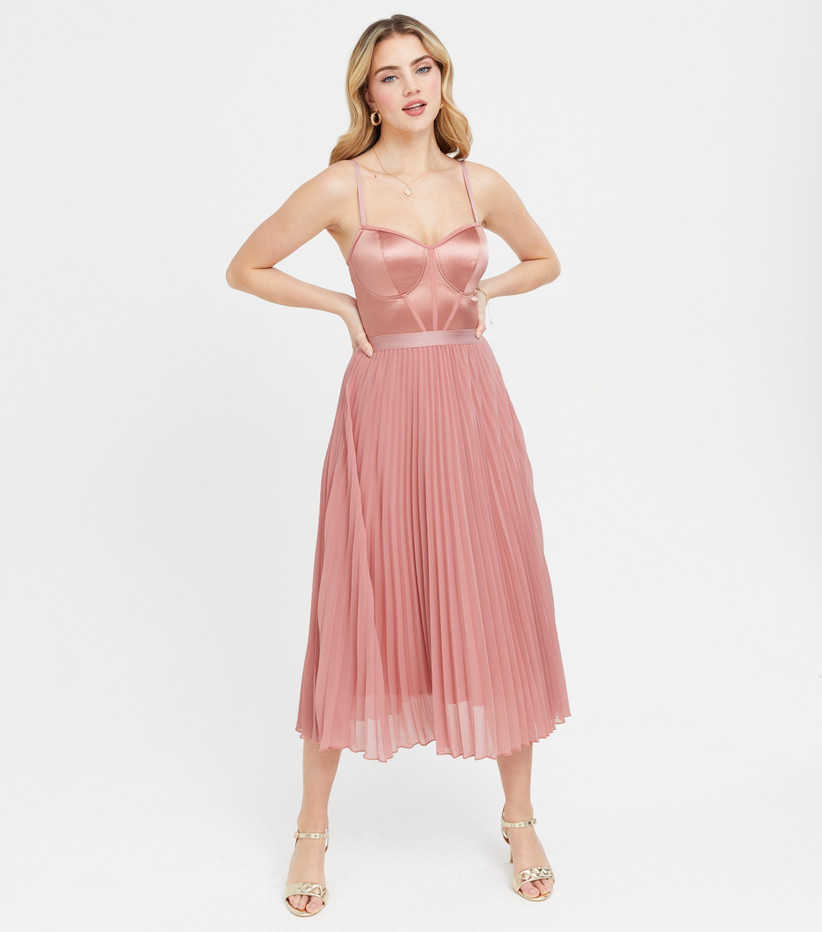 Girl wearing a pink satin dress with pleated skirt