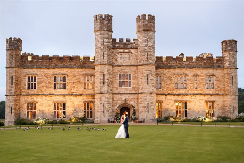 Bride and groom standing outside a grand castle