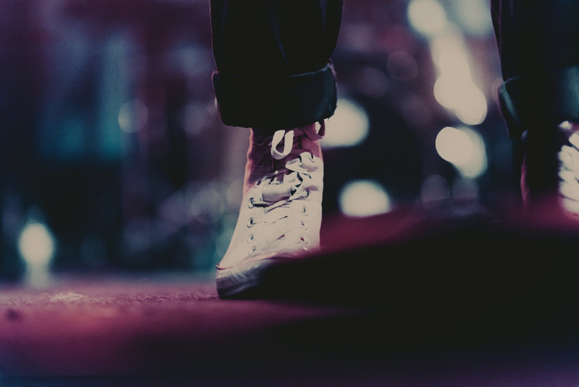 Close up a person wearing rolled up jeans and converse on a lit stage