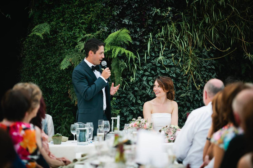 Groom does a speech at a wedding reception with a plant backdrop