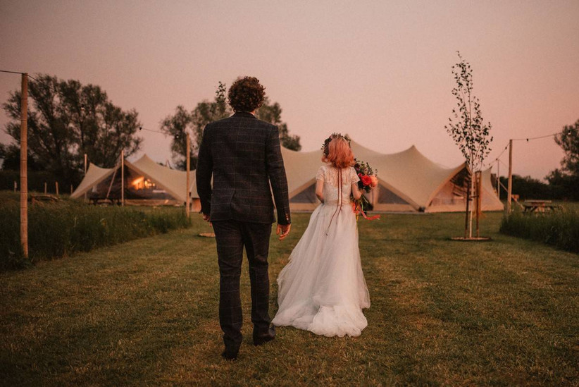 Back view of a bride and groom walking towards a marquee