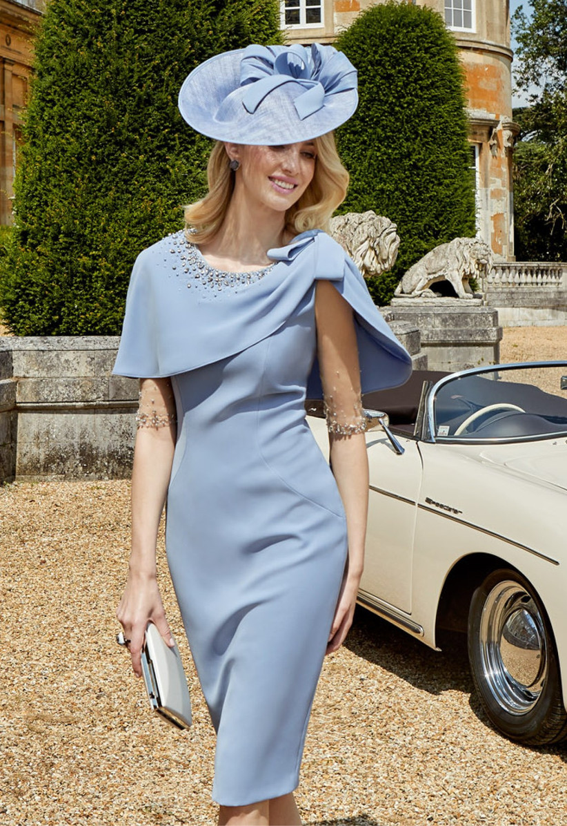 Girl wearing a pale blue caped dress with a hat