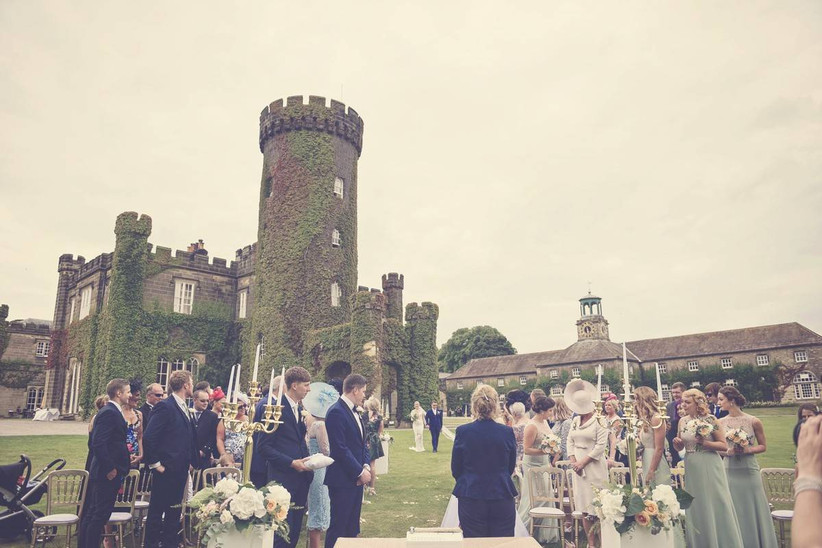 Wedding guests mingle outside an ivy covered castle