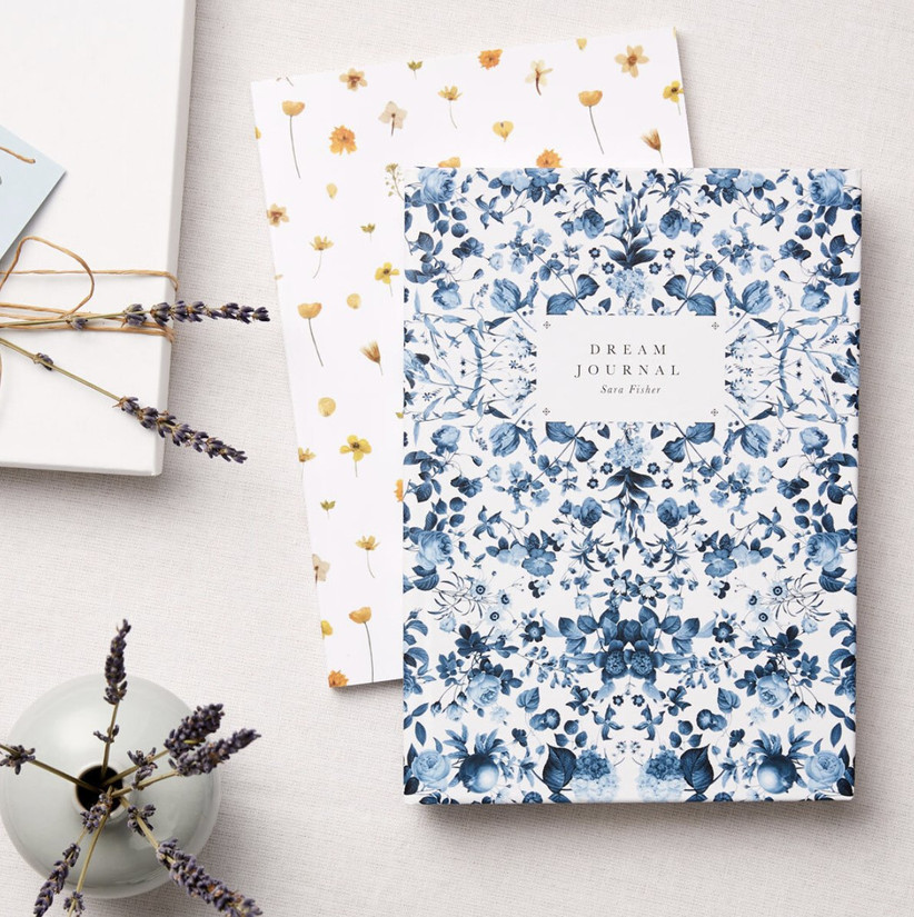 Personalised dream journal with a blue and white floral cover on top of another floral yellow and white journal with sprigs of lavender on a white table