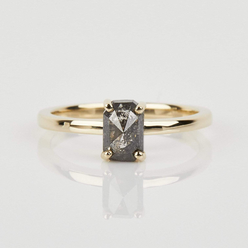 Gold ring with an emerald cut grey diamond at its centre