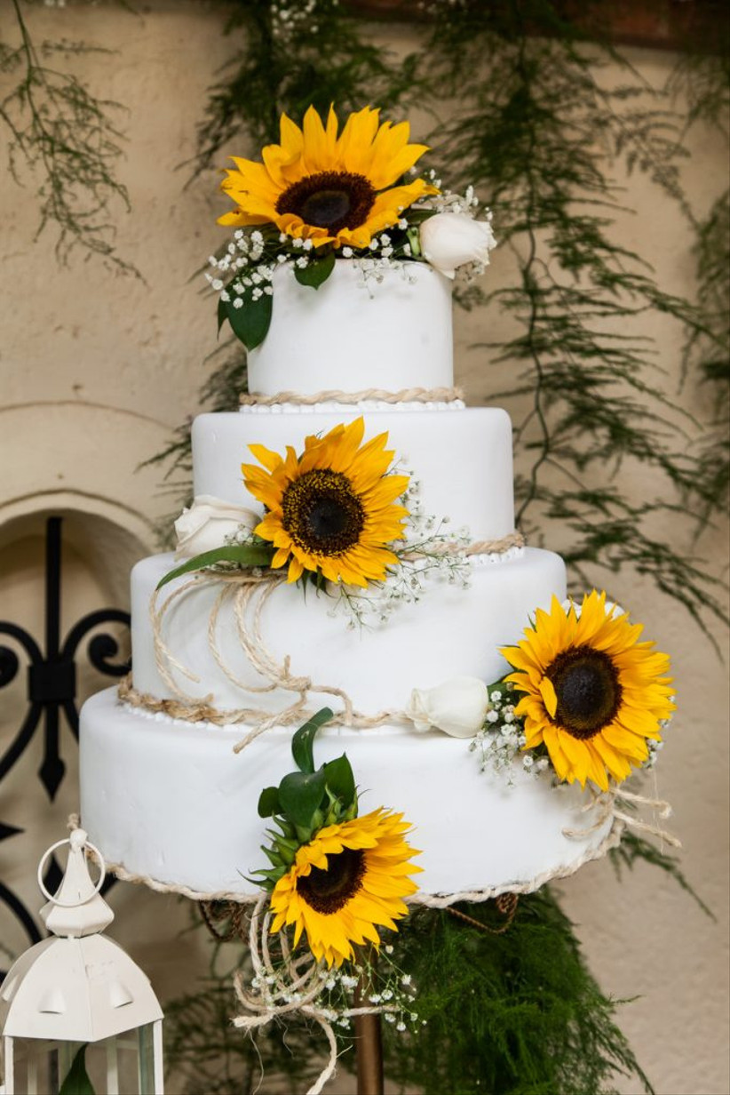 Four tiered white rustic wedding cake with sunflowers and twine