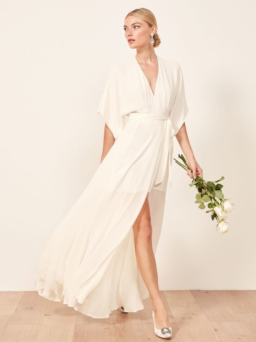 Model wearing a caped white bridesmaid dress holding flowers