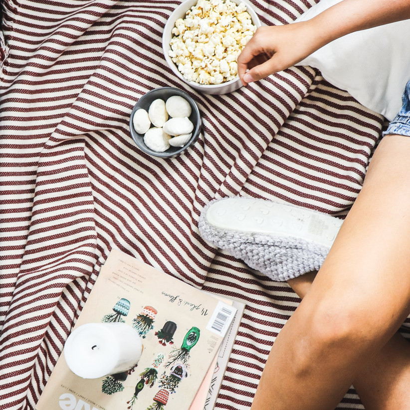 A woman wearing denim shorts and wooly slippers sat on a stripy brown blanket with a bowl of popcorn, meringues, a candle and a magazine