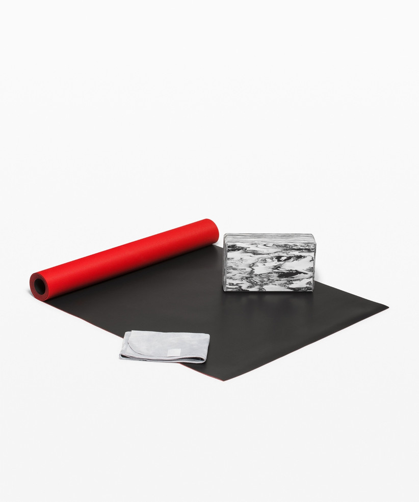 A reversible red and black yoga mat with a marbled grey yoga block and white yoga towel on top of it
