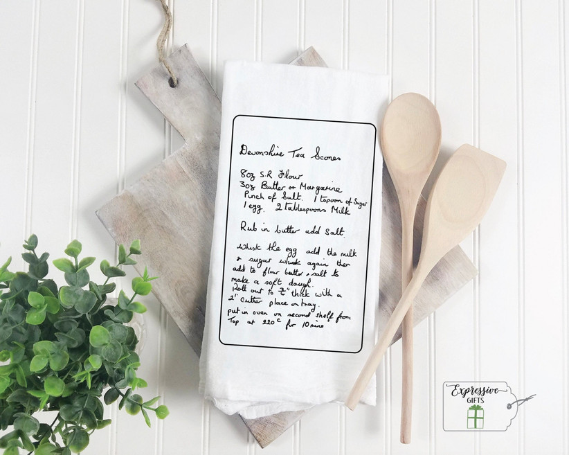 Recipe printed on a tea towel next to wooden spoons and a plant