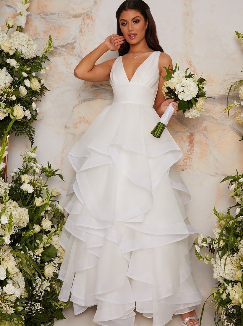 Girl wearing a tiered tulle white wedding dress holding a bouquet of flowers