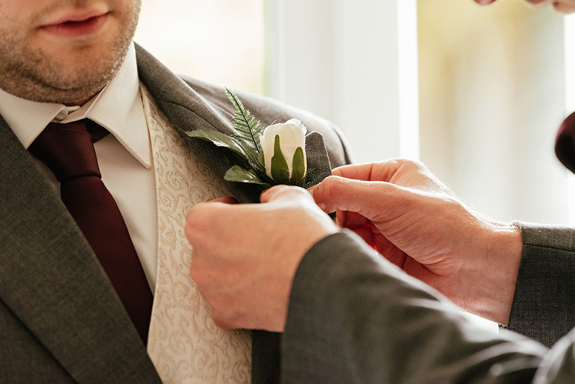 Hands attaching a buttonhole to Ben's suit