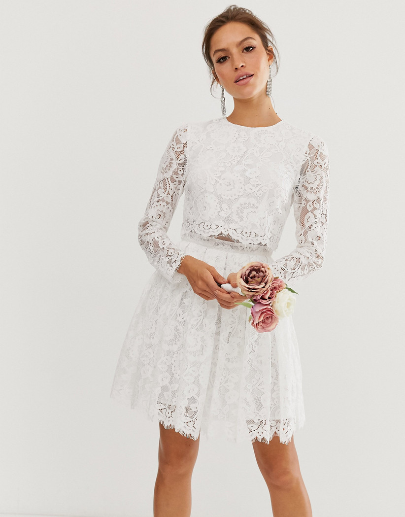 Girl wearing a lace crop top and skirt holding pink roses