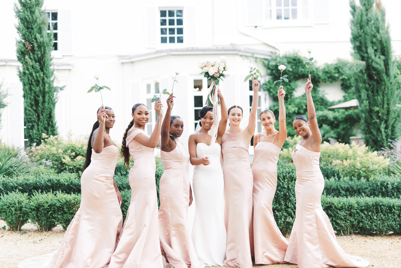 Bridesmaids in pinks holding up flowers