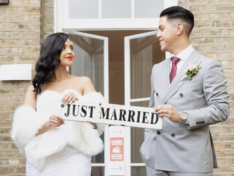Bride and groom Daniella and Jayson holding a 'just married' sign