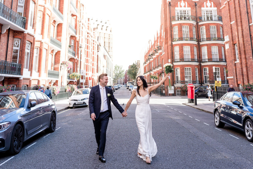 Newly married bride and groom holding hands on a near-empty London street