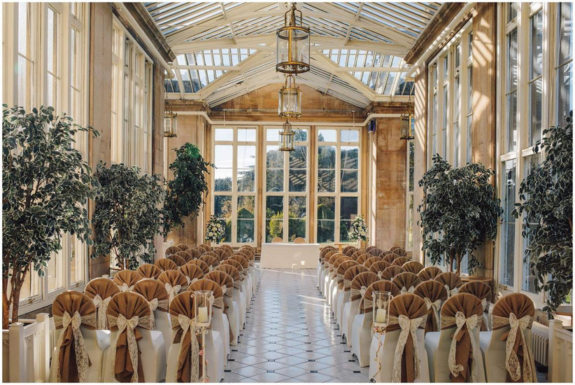 Wedding ceremony in an orangery with tree decorations and bow chairs