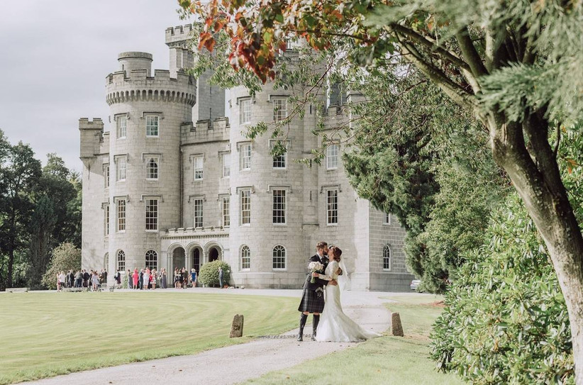 Bride and groom kissing outside a castle