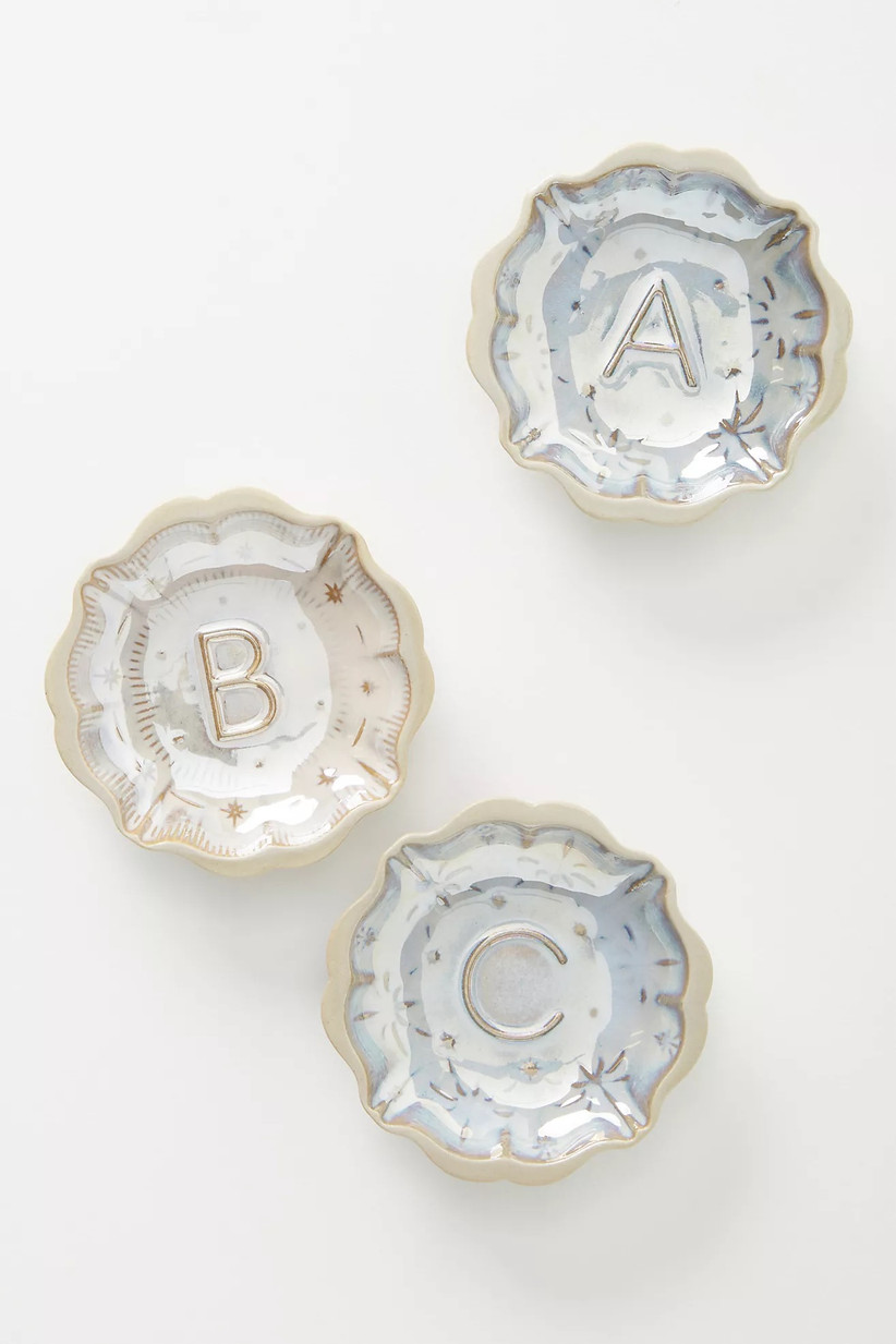 Three monogrammed light blue, gold and cream vintage looking trinket dishes on a white surface