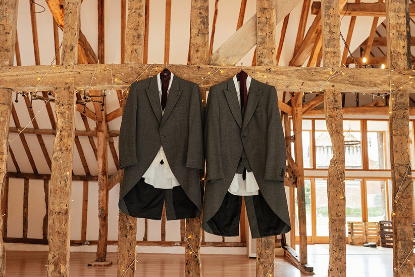 Two grey wedding suits hanging from oak beams