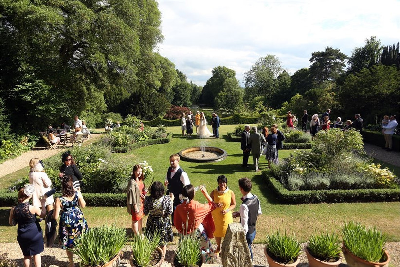 Wedding guests mingling in a manicured garden with a water fountain