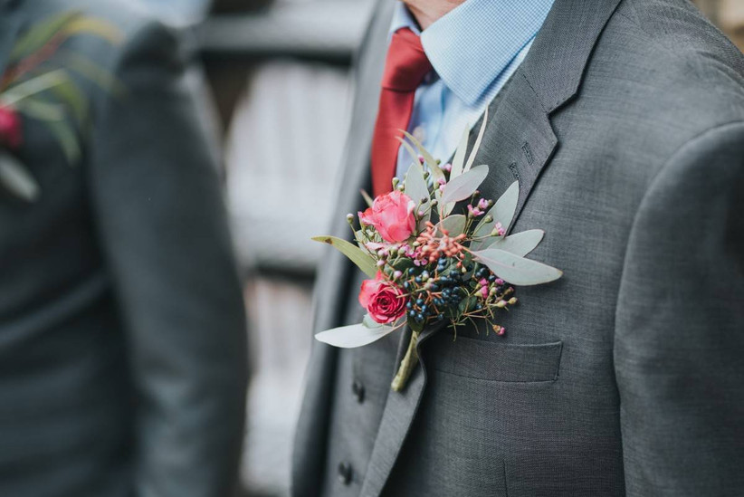 Men's grey suit with red tie and floral buttonhole