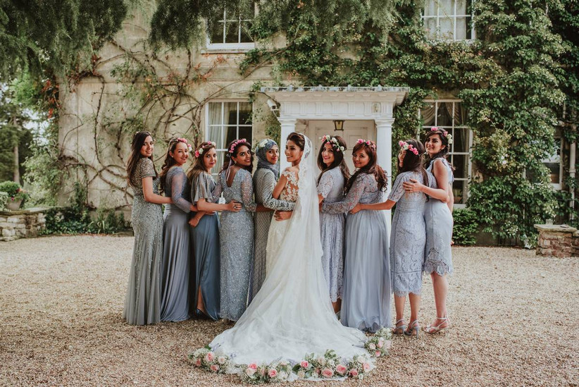 Bride stands with her bridesmaids who are wearing blue dresses