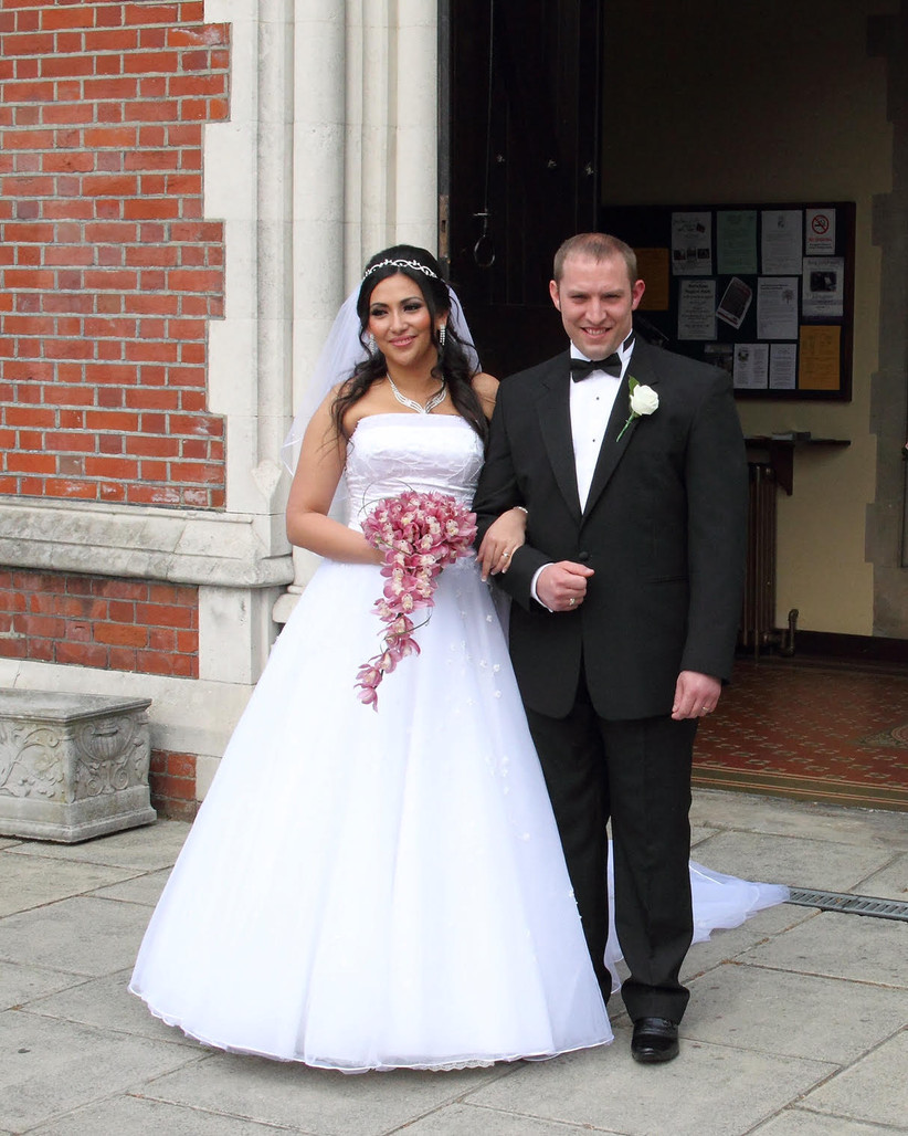 Bride with long dark hair and a white strapless dress poses for a photograph with her husband in a tux on one arm and a pink orchid bouquet in other