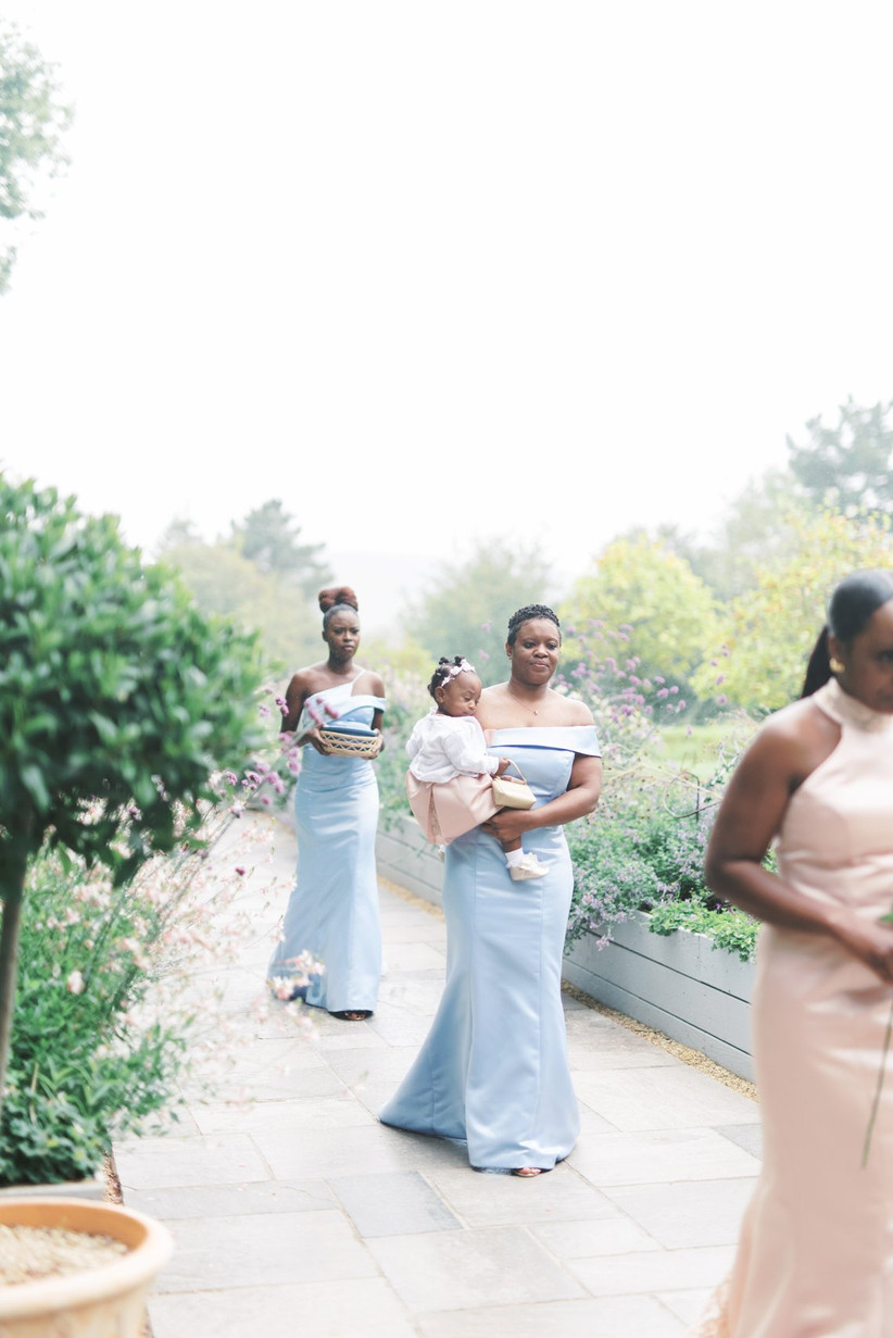 Bridesmaid in blue carrying a baby