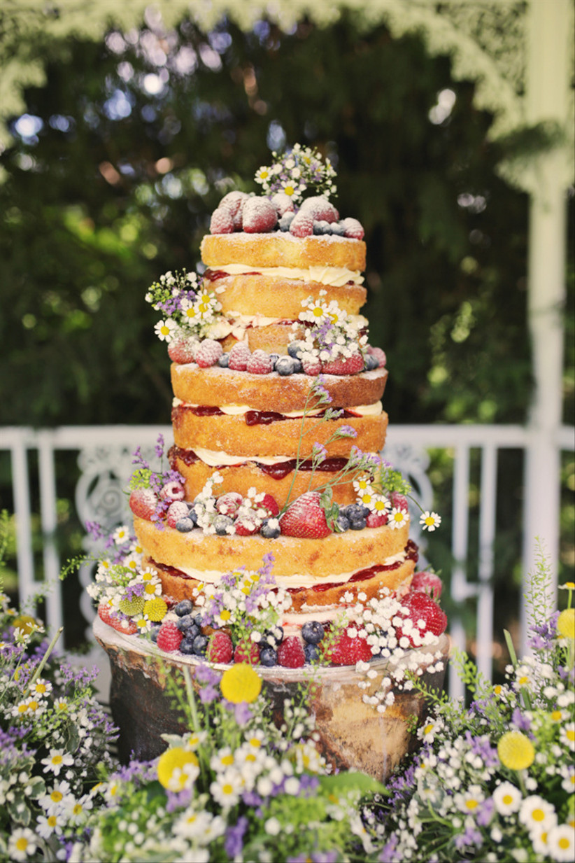 Three tiered victoria sponge rustic wedding cake with icing sugar, daisies and fruit