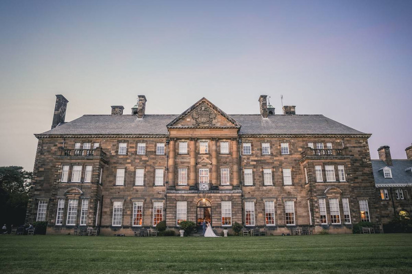 Stately wedding venue with a bride and groom standing outside