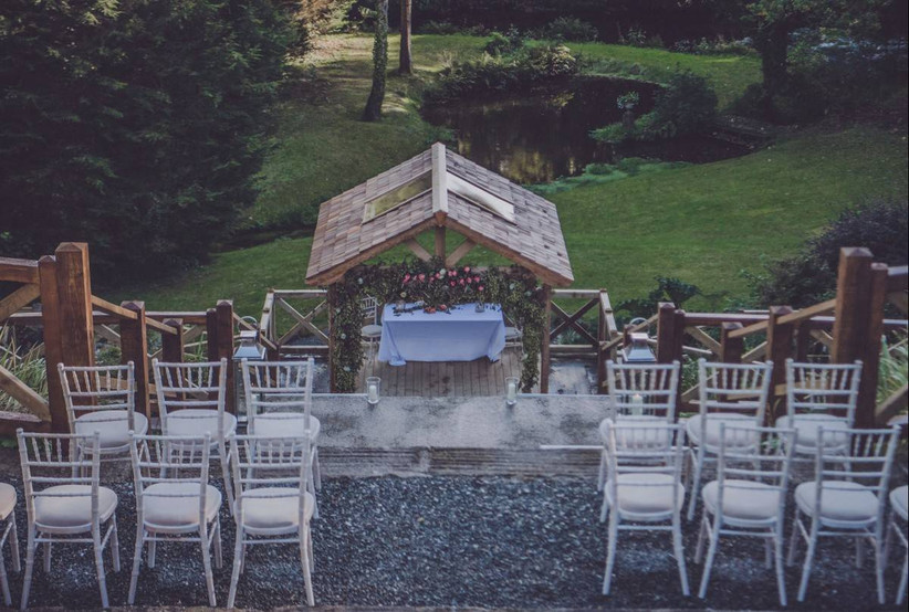Outside wedding ceremony chairs with a wooden gazebo