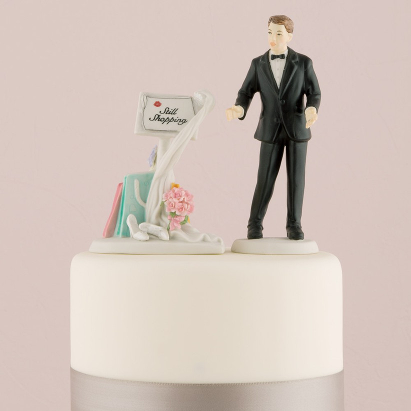 Groom next to a still shopping sign wedding cake topper