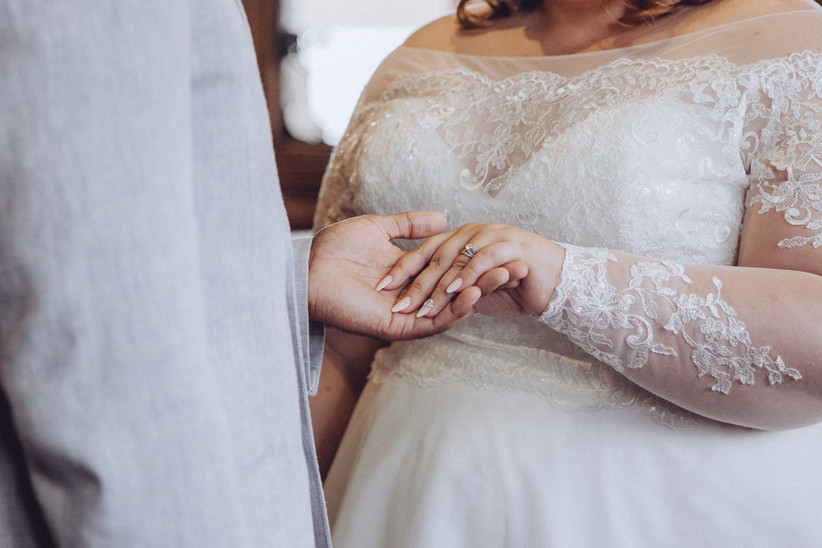Bride in a plus size wedding dress holding hands with a groom in a blue suit