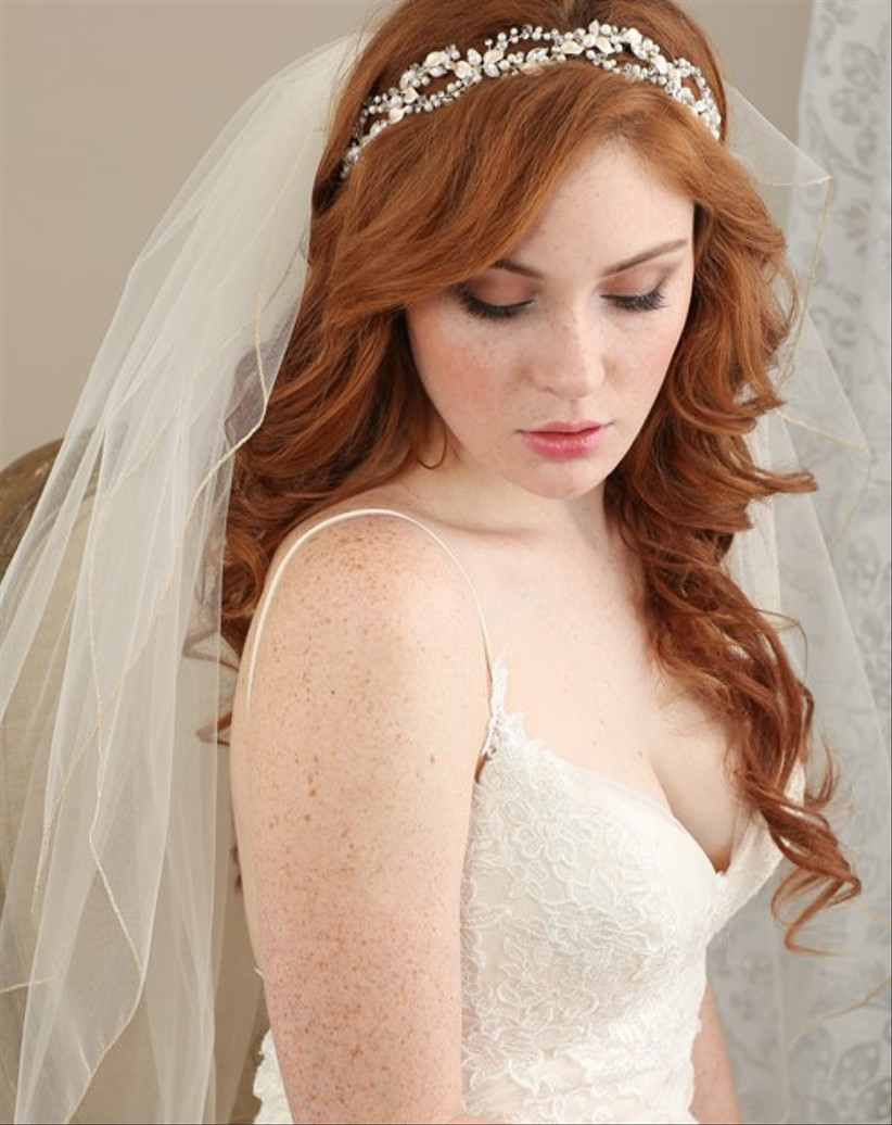 Bride with a sweeping fringe half up half down hairstyle and veil