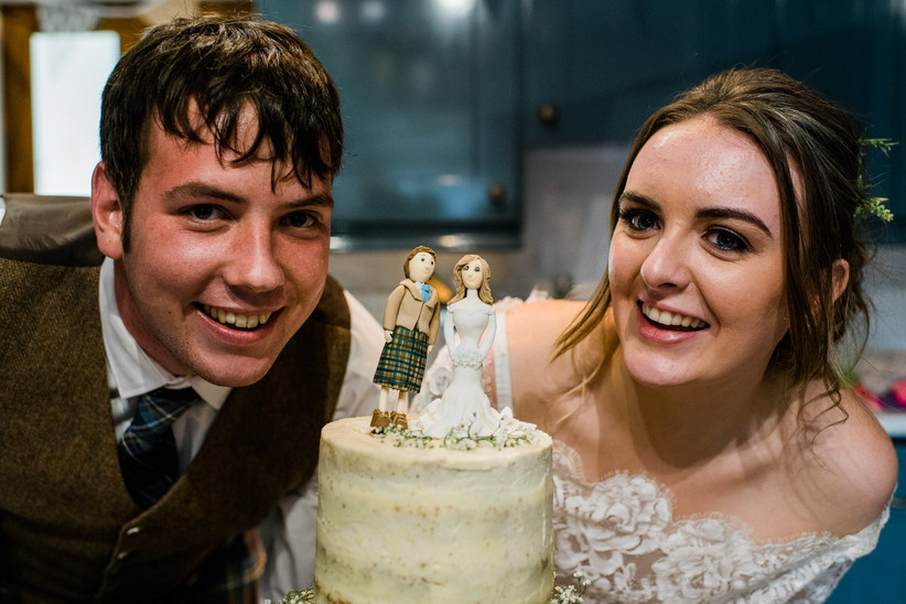 Caitlin and Stephen smiling next to their buttercream wedding cake