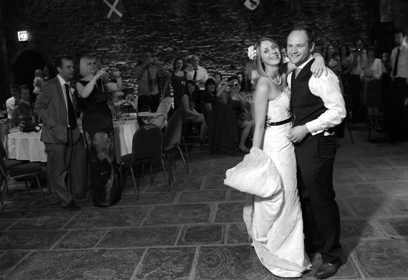 Black and white photo of a smiling white bride with a bob and flower in her hair in a strapless white wedding gown with her arms around her white groom on a stone dance floor