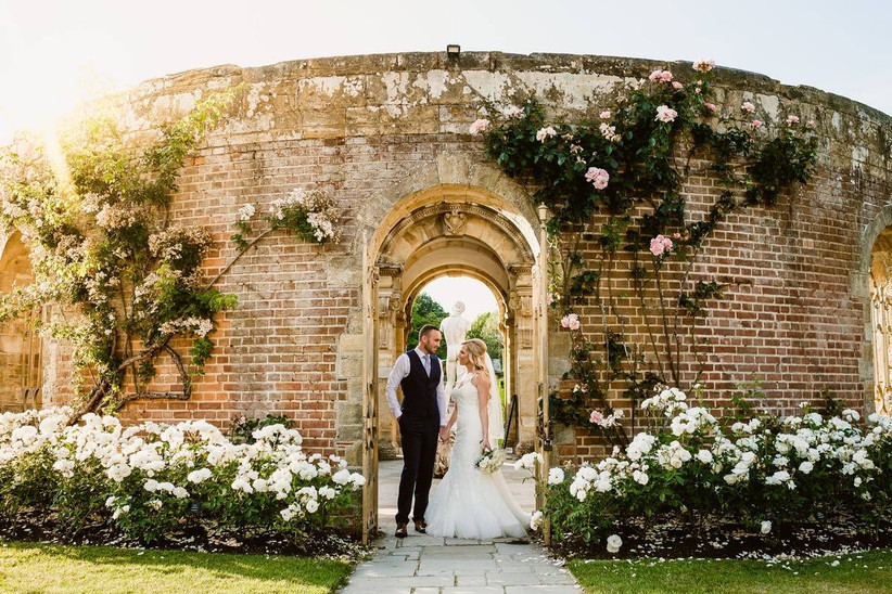 Bride and groom hold hands under a stone rose covered archway