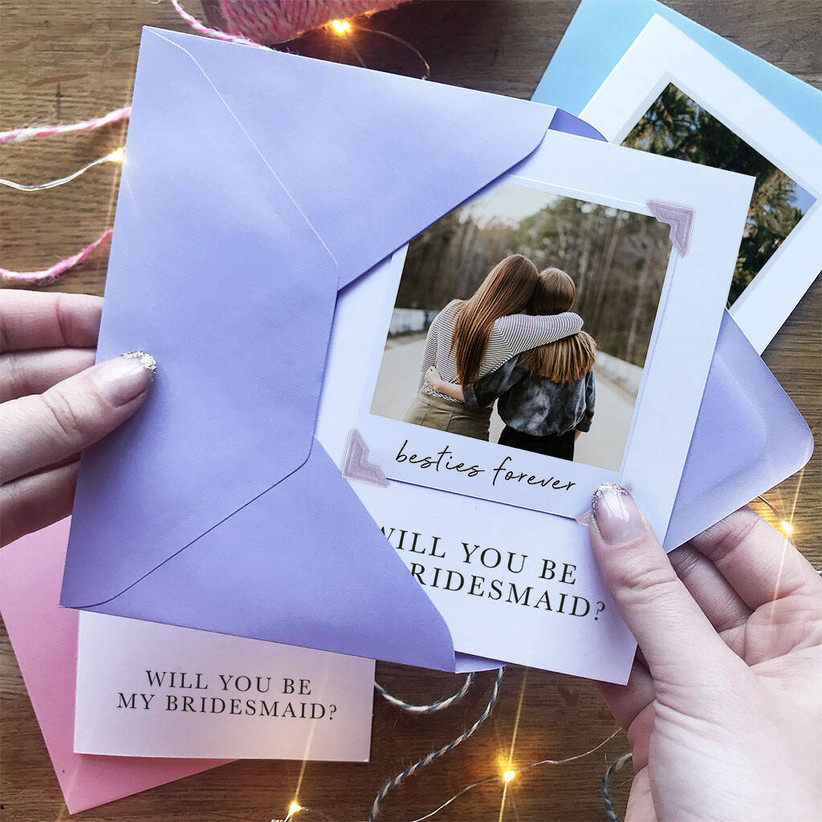 White card featuring a polaroid photo of two women buggies with a will you be my bridesmaid message and a besties forever note