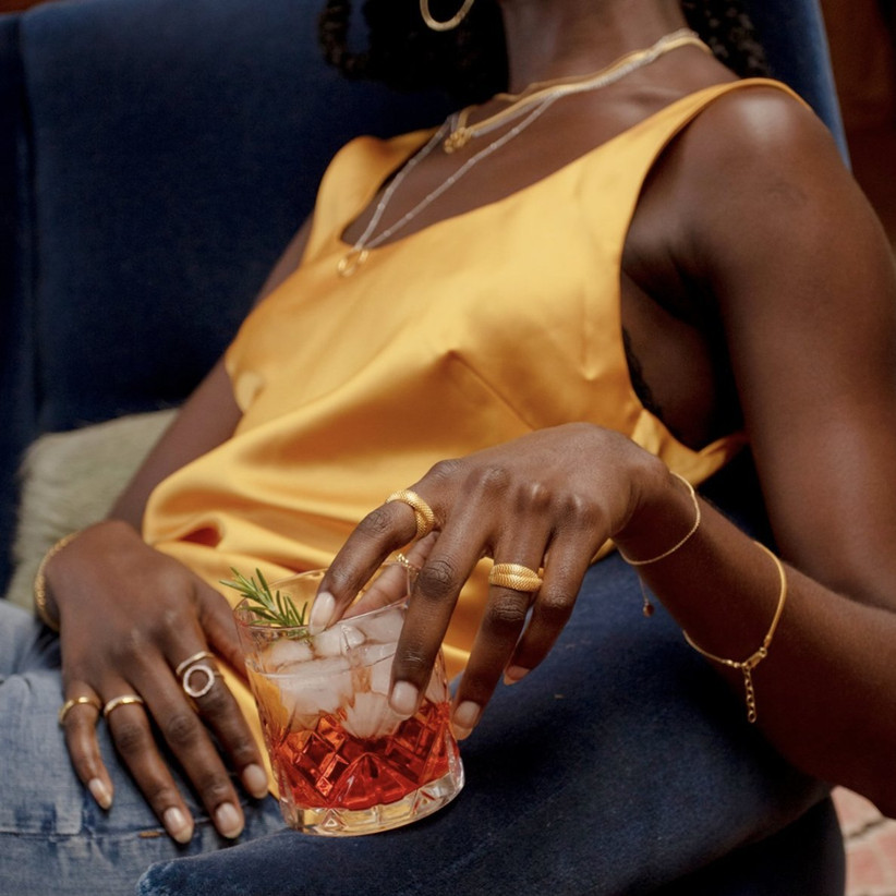 Woman in a yellow top with gold jewellery holding a crystal class with an orange cocktail, ice and a sprig of rosemary