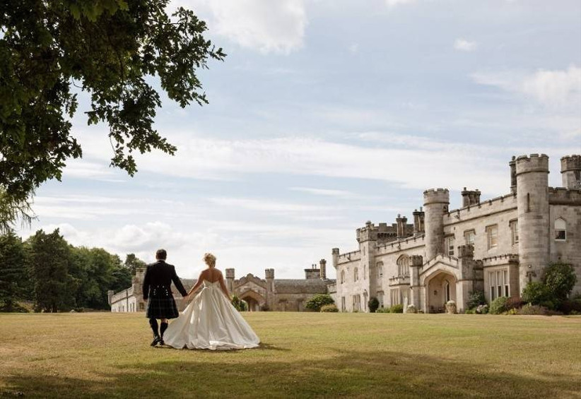 Outside view of a castle with a bride and groom hand in hand