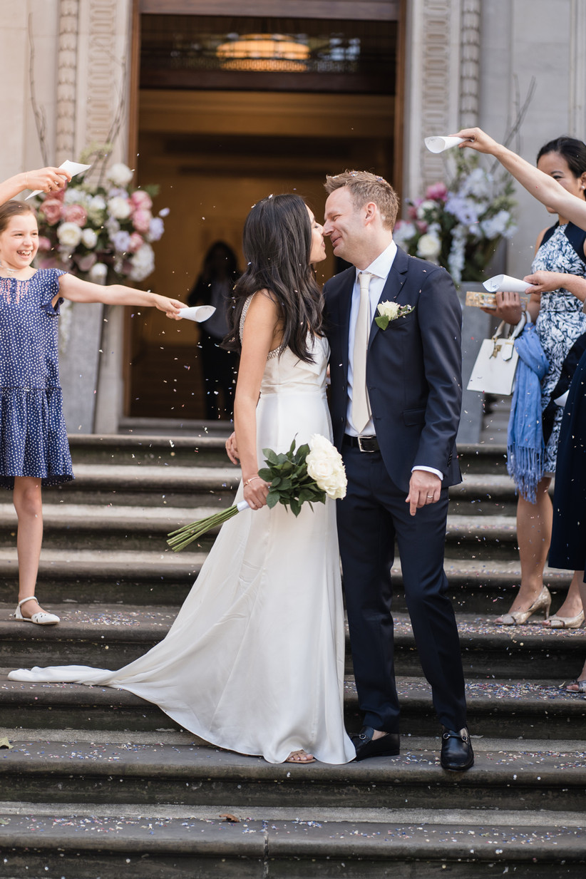 Bride and groom on steps as guests throw confetti