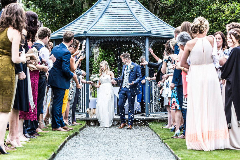 Bride and groom marry in an outside pavilion and are showered with confetti from guests