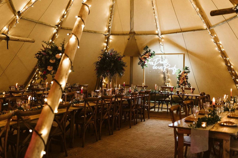 Dining area in a wedding tipi decorated in fairy lights