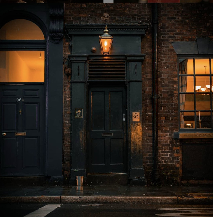 A dark teal door with a gas lamp above it on a brick street at dusk with a gold bar sign