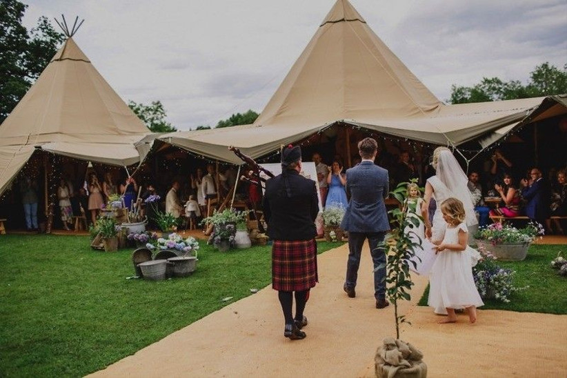 Bride, groom and wedding guests outside a wedding marquee