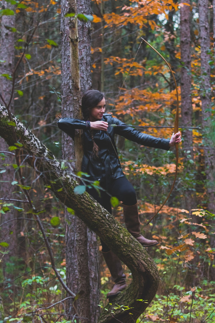 White woman with long dark hair in a plait over her shoulder balanced in a tree drawing back a bow and arrow wearing a dark blue anorak and dark blue trousers