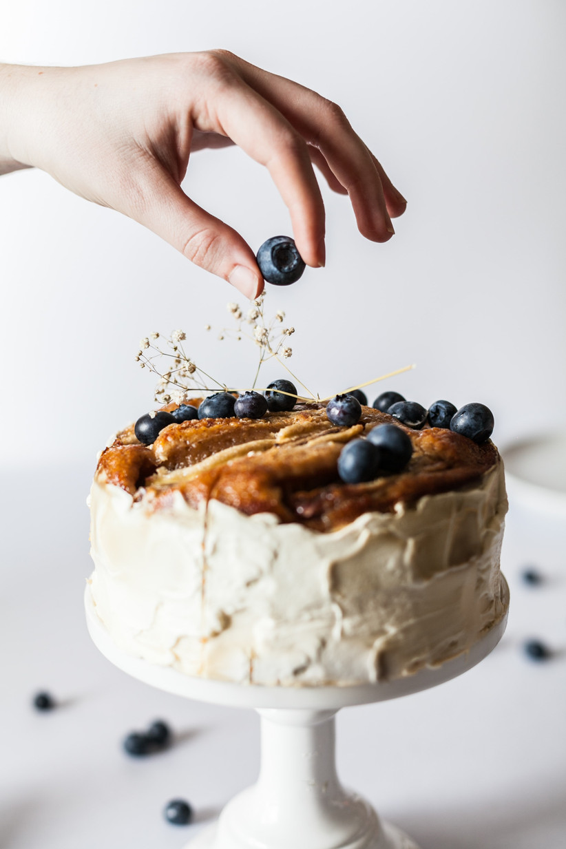 Close up of white hand adding a blueberry to the top of a white roughly iced cake