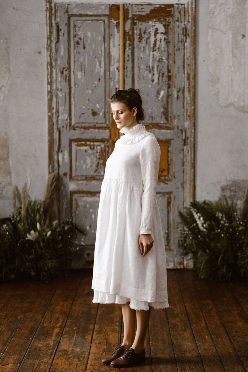 Model wearing a white linen maternity dress with a high ruffled neck