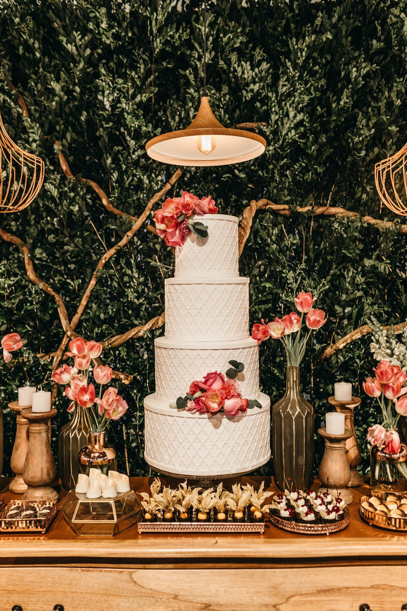 Wedding dessert table with a white three-tier wedding cake as the centrepiece